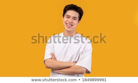 portrait of a young smiling asian man with arms folded over white background stock photo © deandrobot
