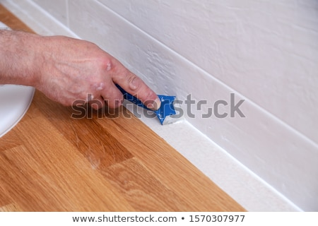 Stock photo: Worker caulking bath tube and tiles