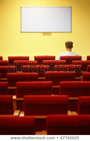Empty conference hall. rows of a chairs. focus on a first row. one man sitting in chair Stock photo © Paha_L