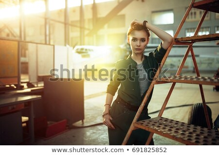 mechanic in overall standing and looking at camera near airplane stock photo © deandrobot