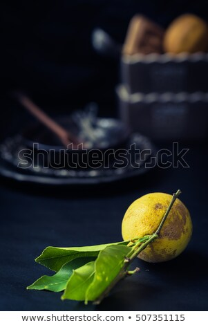 organic lemon and kitchenware blurred on dark background Stock photo © faustalavagna