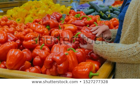 Woman selecting and buying bell pepper in grocery shop Stock photo © deandrobot