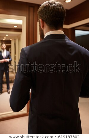 Vertical image of bearded man correcting his suit against mirror Stock photo © deandrobot