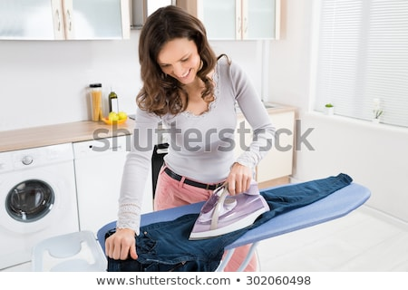 Caucasian maid ironing clothes on ironing board. Stock photo © RAStudio