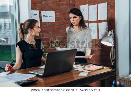 Boss assisting her employee with documents Stock photo © deandrobot