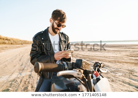 Smiling bearded man in sunglasses sitting on modern motorbike stock photo © deandrobot
