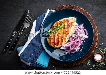 Juicy grilled chicken meat, fillet with fresh marinated onion on plate. Black background, top view Stock photo © yelenayemchuk