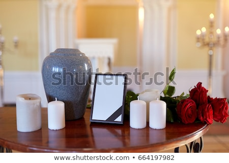 photo frame cremation urn and candles on table stock photo © dolgachov