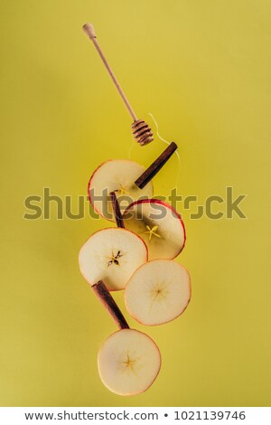 close up view of levitating pieces of apple, cinnamon sticks and honey Stock photo © LightFieldStudios