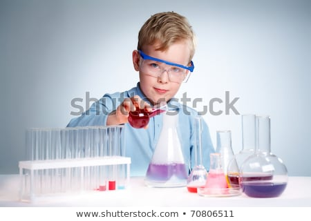 Boy pouring liquid from a tube and into a flask. Stock photo © RAStudio