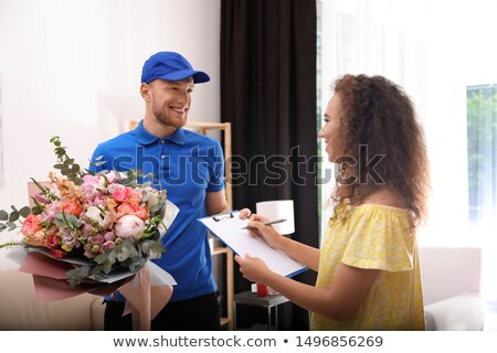 delivery man with beautiful flower bouquet gift stock photo © kzenon