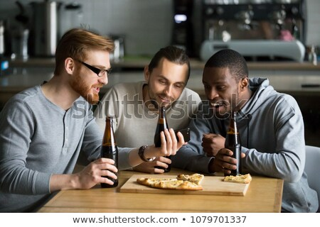 man with smartphone and bottle of beer at home Stock photo © dolgachov