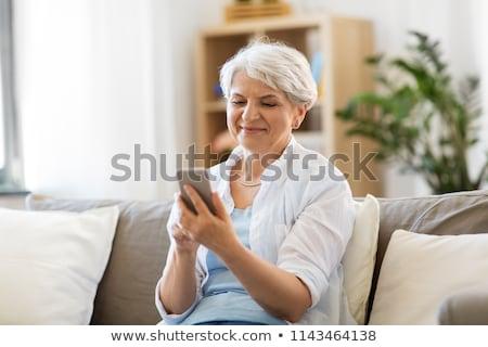 женщину · смартфон · гостиной · улыбающаяся · женщина · улыбаясь - Сток-фото © dolgachov