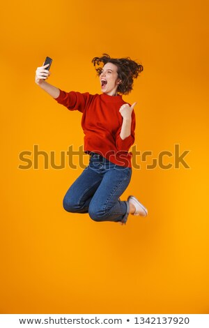 Image of joyous curly woman 20s smiling and taking selfie photo  Stock photo © deandrobot