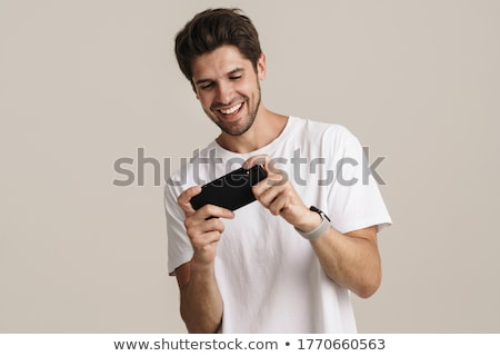 Jóképű izgatott fiatal szakállas férfi áll Stock fotó © deandrobot