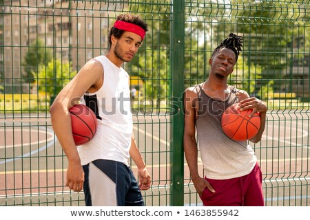 Two active guys in sportswear standing by fence surrounding basketball court Stock photo © pressmaster