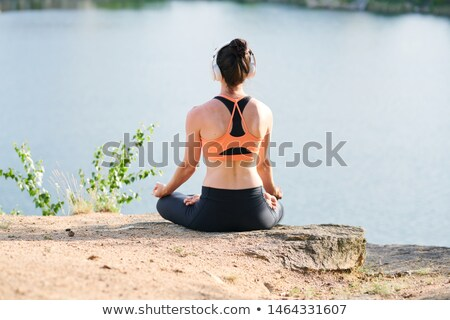Rear view of young woman in wireless headphones sitting in lotus position Stock photo © pressmaster