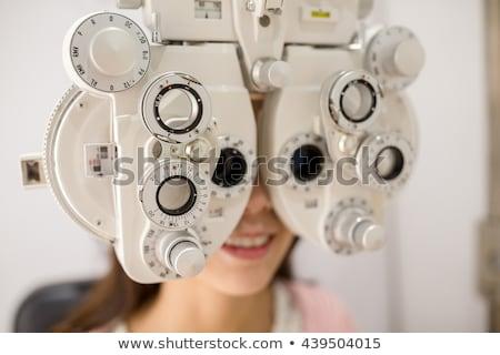 Young optometrist looking through lens of eyesight check-up equipment Stock photo © pressmaster
