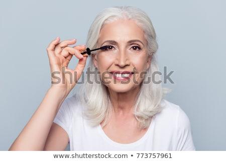 smiling senior woman applying mascara to eyelashes Stock photo © dolgachov
