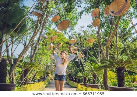 Young woman tourist and Vietnamese hats. Travel around Vietnam concept Stock photo © galitskaya