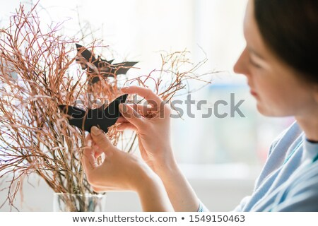 Young woman hanging handmade bats on dry branches while preparing decorations Stock photo © pressmaster