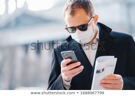 Outdoor shot of serious man manager focused in cellular display, reads news online, holds newspaper, Stock photo © vkstudio