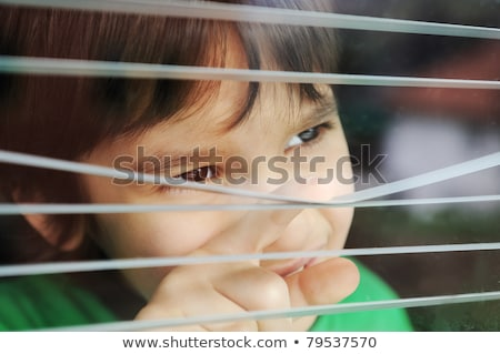 Portrait of an innocent small boy peeping through window with jalousie Stock photo © zurijeta
