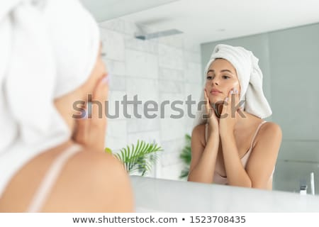 Beautiful brunette after spa applying moisturizer. Stock photo © lithian
