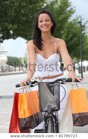Woman on a pushbike laden down with store bags Stock photo © photography33