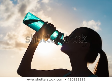Teenager drinking water on the beach Stock photo © photography33