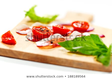 Dried cherry tomatoes with bacon served on carving board.  Stock photo © dariazu