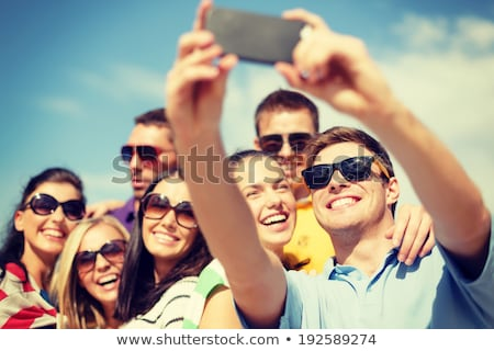 Foto d'archivio: Group Of Smiling Women Photographing On Beach