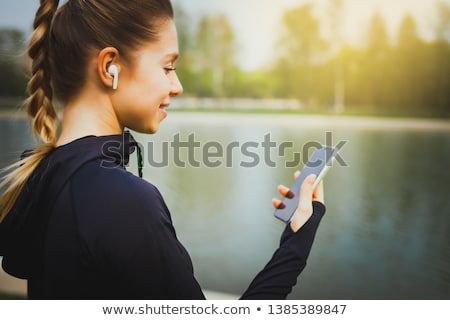 Young Beautiful Sports Woman Using her Phone in the Park Stock photo © maxpro