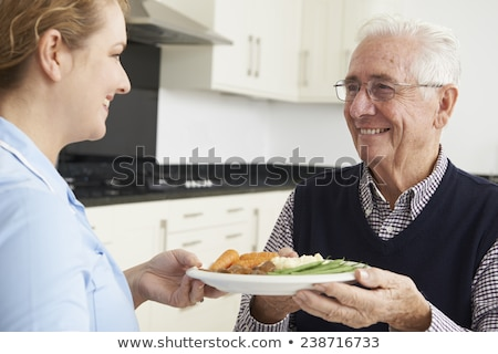 carer serving lunch to senior man stock photo © highwaystarz