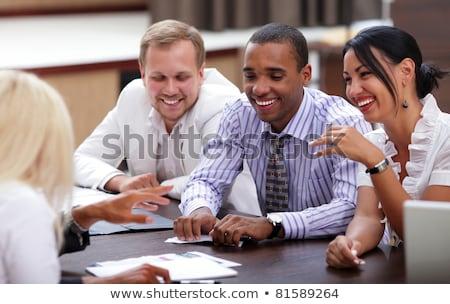 Mutlu iş adamları oturma etrafında tablo toplantı Stok fotoğraf © deandrobot