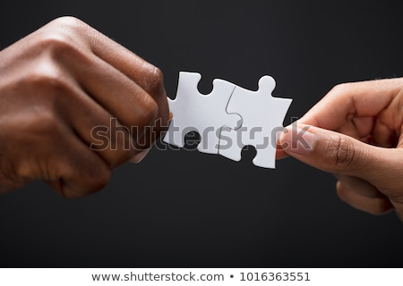 close up of a person joining two jigsaw pieces stock photo © andreypopov