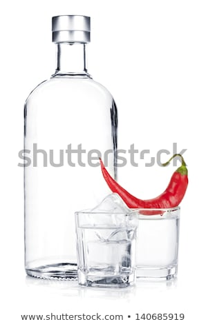 bottle of vodka with red pepper and glass isolated on white Stock photo © tetkoren