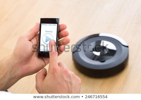 Man controlling vacuum cleaner with smartphone. Stock photo © RAStudio