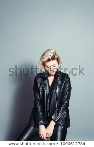 sad dramatic biker in leather jacket sitting stock photo © feedough