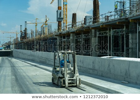 Construction site with man driving folklift Stock photo © bluering