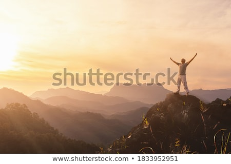 hiking or climbing success with arms raised in mountains stock photo © blasbike