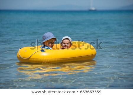 Lány felfújható csónak tenger naplemente test Stock fotó © alphaspirit