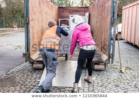 Woman and man giving electrical appliances to recycling center Stock photo © Kzenon