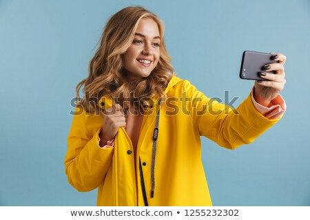 Image of content woman 20s wearing yellow raincoat holding cell  Stock photo © deandrobot