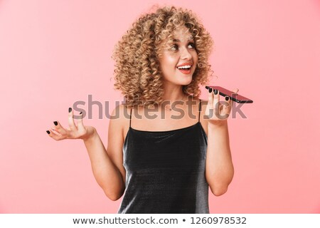 Image of positive woman 20s with curly hair talking on smartphon Stock photo © deandrobot