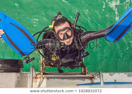 Happy diver returns to the ship after diving Stock photo © galitskaya
