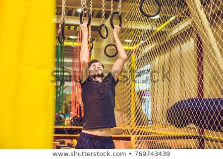 The man passes the obstacle course in the sports club Stock photo © galitskaya