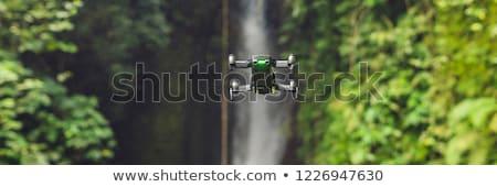 Little quadcopter flying around waterfall Leke Leke Bali island Indonesia Stock photo © galitskaya