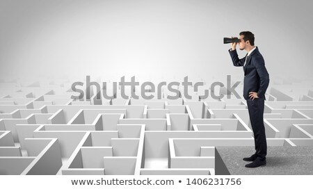 Man standing on top of a maze with binoculars Stock photo © ra2studio