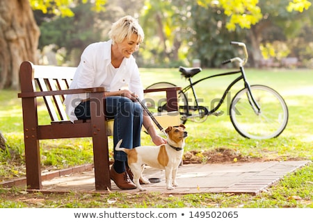 Image of caucasian woman sitting on bench in park with bicycle,  Stock photo © deandrobot